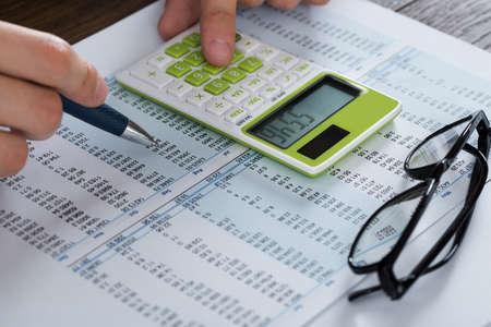 calculadora: Primer plano de la persona Manos Analizar Contabilidad Documento Con La Calculadora