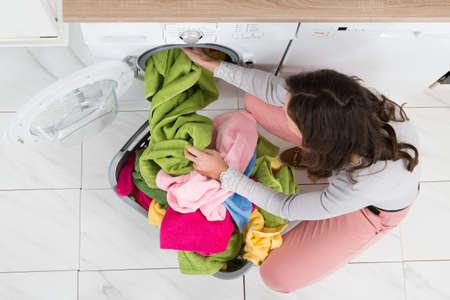 Hoog standpunt Van Jonge Vrouw Laden bonte kleren In Washer
