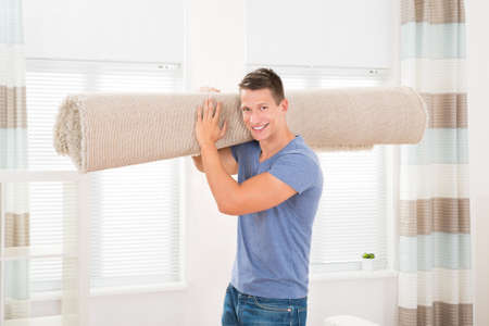 blind man: Portrait Of Happy Young Man Carrying Rolled Carpet