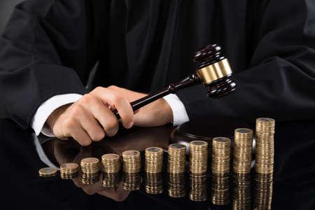 incremento: Primer plano de la jueza Manos Golpear Mazo delante de monedas apiladas en el escritorio