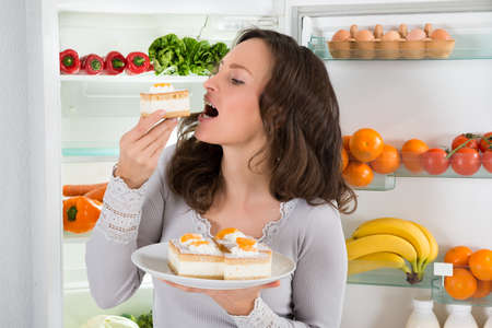 Junge Frau isst Scheibe des Kuchens nahe dem offenen Kühlschrank Standard-Bild