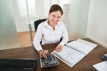 account executives: Photo Of Happy Businesswoman Calculating Invoice At Desk