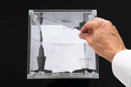 hand paper: High Angle View Of Person Hands Putting Voting Ballot In A Slot Of Box Stock Photo