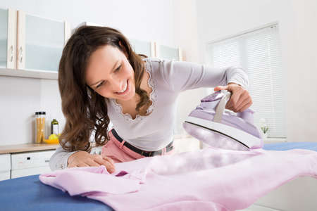 Happy Woman Ironing Cloth With Electric Iron In Kitchen Stockfoto