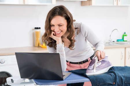 usando computadora: Mujer Feliz Mirando a la computadora portátil mientras paño de planchar En tabla de planchar