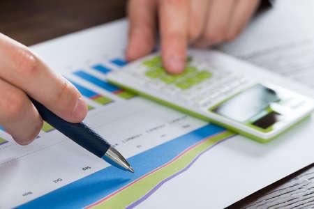 calculadora: Close-up persona Manos análisis de informe financiero con la calculadora
