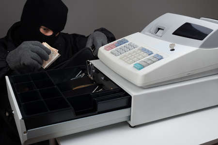 Burglar In Balaclava Mask Stealing Money From Cash Register