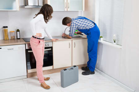 overall: Young Woman Looking At Plumber In Overall Fixing Sink In Kitchen Stock Photo