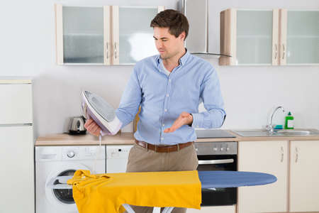 unhappy man: Unhappy Young Man With Electric Iron And Yellow T-shirt Standing In Kitchen Room
