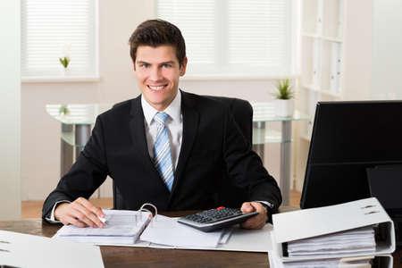 ejecutiva en oficina: Hombre de negocios feliz joven Cálculo de Datos Financieros En El Escritorio