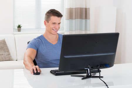 Young Happy Man Using Desktop Computer In Living Room