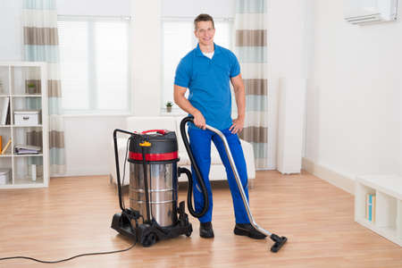 wooden floor: Happy Male Janitor Vacuuming Wooden Floor In House
