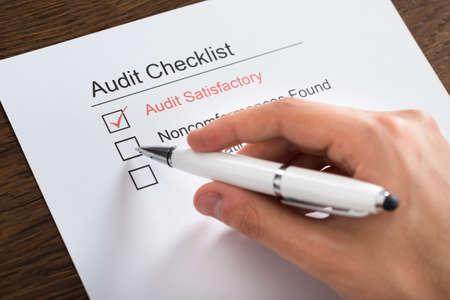 auditor�a: Primer plano de la persona Manos Llenar Formulario de Lista de comprobaci�n de Auditor�a con la pluma en el escritorio