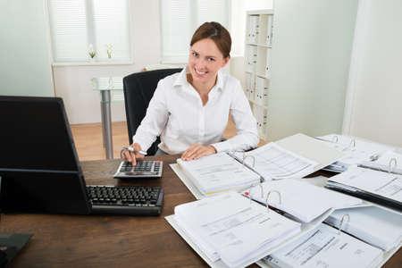 auditoría: Empresaria feliz calcular los datos financieros con la calculadora en el escritorio