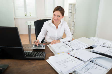 Happy Businesswoman Calculating Financial Data With Calculator At Desk