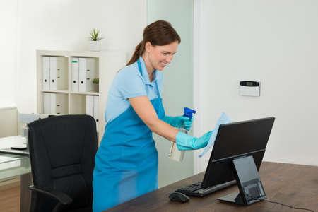personal de limpieza: Feliz Joven Mujer Conserje Limpieza escritorio de madera con trapo En Office