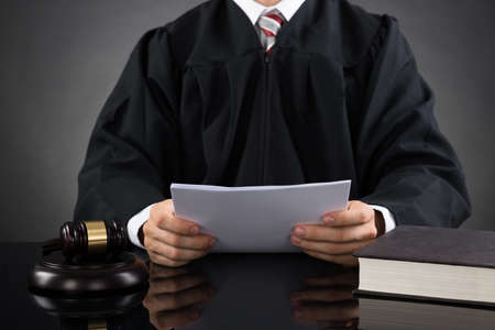 robes: Close-up Of Male Judge Reading Paper In Courthouse