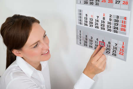 calendar date: Close-up Of Young Businesswoman Placing Red Mark On Calendar Date