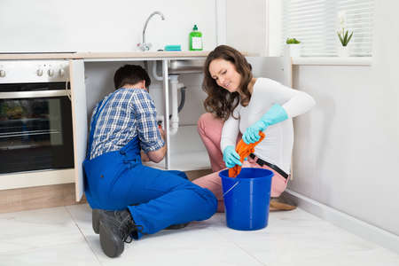 leakage: Repairman Fixing Pipe Under Sink While Woman Squeezing Wet Cloth In Kitchen Stock Photo