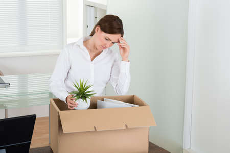 transferred: Unhappy Businesswoman Packing Her Belongings In Cardboard Box At Desk