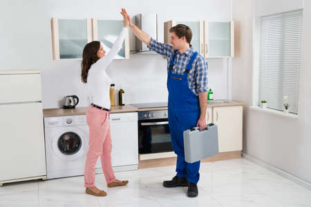 high five: Young Woman Giving High Five To Repairman With Toolbox In Kitchen Stock Photo