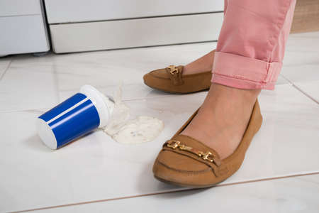spread legs: Close-up Of Female Leg Wearing Brown Footwear Standing Near The Yoghurt Spilled On Floor