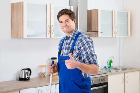 happy worker: Young Happy Worker In Overall Mopping Floor Stock Photo