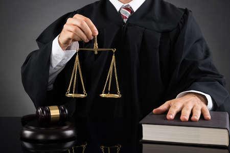 martillo juez: Primer Del Juez masculino que sostiene la escala del peso de oro en el escritorio Foto de archivo