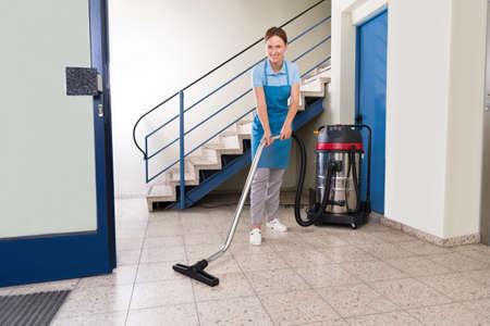 Junge Weibliche Hausmeister Reinigung Boden mit Staubsauger Standard-Bild - 44714103