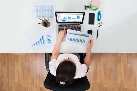 High Angle View Of Businesswoman Working With Graphs At Desk Stock Photo - 44714112