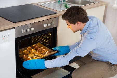 oven: Young Man Taking Baking Tray With Baked Bread From Oven In Kitchen