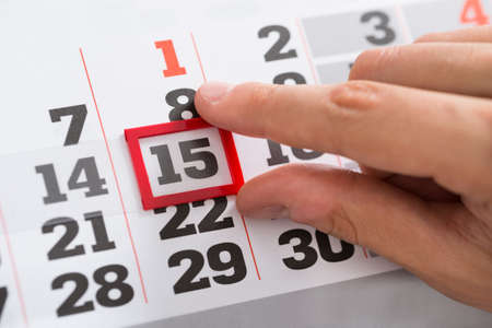 Close-up Of Person Hands Making A Red Mark On Calendar Date 스톡 콘텐츠
