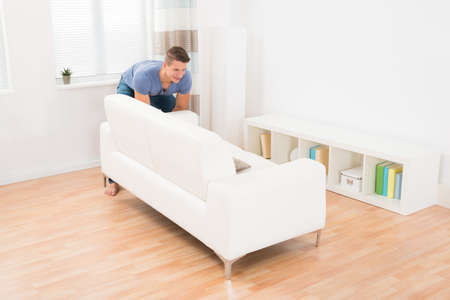 one man: Young Happy Man Moving Sofa In Living Room