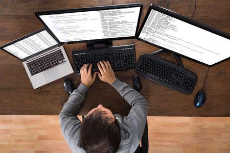 datos personales: Hombre joven que roba datos de los ordenadores y port�til en el escritorio Foto de archivo