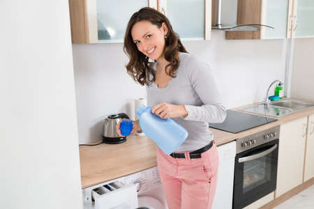 household chores: Young Happy Woman Pouring Liquid Detergent In The Bottle Cap