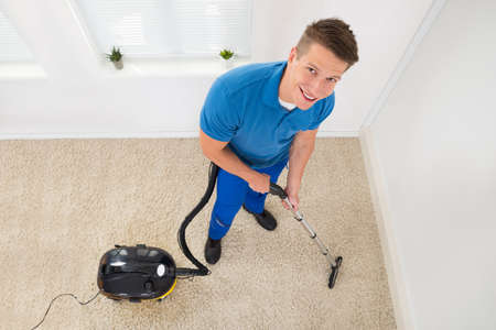 clean carpet: High Angle View Of Happy Worker Vacuuming Carpet Stock Photo