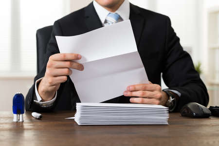 postal: Close-up Of Businessman Holding Document At Desk In Office