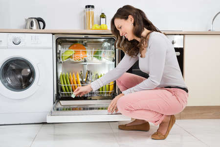 Happy Woman Putting Detergent Tablet In Dishwasher At Home