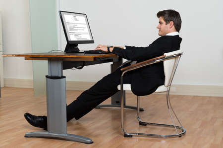 businessman working at his computer: Businessman Leaning Back In His Chair While Working On Computer In Modern Office Stock Photo