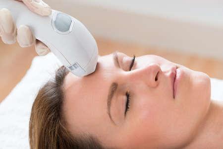 Close-up van schoonheidsspecialiste geven Laser ontharing behandeling van jonge vrouw gezicht