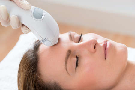 tratamiento facial: Primer De Esteticista Dar tratamiento de depilaci�n l�ser a la mujer joven Cara Foto de archivo