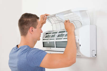 condition: Young Man Checking Air Conditioner Mounted On White Wall