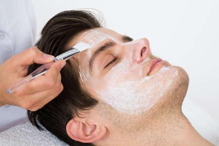 tratamiento facial: Las manos del terapeuta con cepillo Aplicar la mascarilla a un hombre joven en un spa