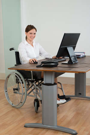 Happy Businesswoman Sitting On Wheelchair While Working On Computer At Desk