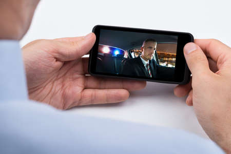 Close-up Of Person Watching Video On Mobile Phone