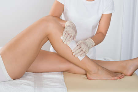 depilate: Beautician Waxing Leg Of Woman With Wax Strip At Beauty Clinic