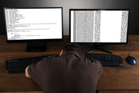 boring: Man Sleeping At Desk With Computers Showing Program Code Stock Photo