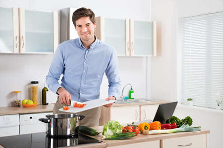 Young Handsome Man Preparing Food In Kitchen At Home