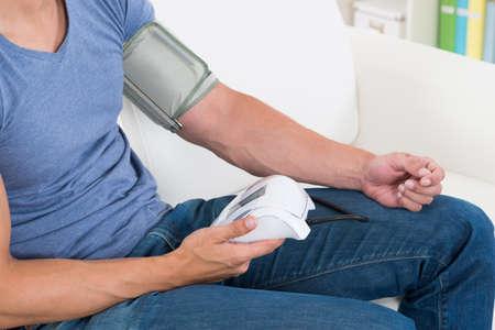 hipertension: Primer plano del hombre joven que se mide su presión arterial en casa Foto de archivo