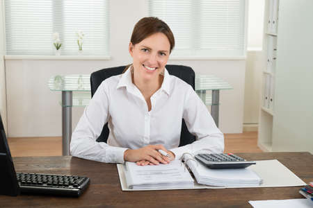 accounts: Photo Of Happy Businesswoman Calculating Invoice At Desk